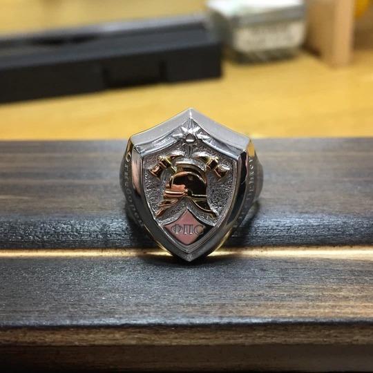 Серебряный перстень с пожарной символикой на столе